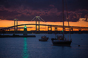 """The Green light on Goat island shines through a dramatic dark sunset from """"The point"""" section of Newport, RI looking at the Newport Pell Bridge"""