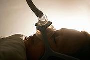 Nederland, Ubbergen, 2-11-2016Slapende vrouw met zuurstofmasker ter voorkoming van slaapapneu. (vrouw is echtgenote van fotograaf). Continious Positive Airway Pressure, apparaat dat met behulp van lucht door een masker te blazen de luchtweg openhoudt. Behandeling van ernstig osas .Foto: Flip Franssen