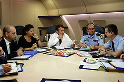 France's President Emmanuel Macron, center, confers with officials aboard the presidential plane en route to Guadeloupe Island, the first step of his visit to French Caribbean islands, Tuesday, Sept. 12, 2017. Seated at the table from left are French Education Minister Jean-Michel Blanquer, French Minister for Solidarity and Health Agnes Buzyn, Director General of the Gendarmerie Nationale, Richard Lizurey, director of the rescue service (Securitª Civile), Jacques Witkowski. Photo by Christophe Ena/Pool/ABACAPRESS.COM