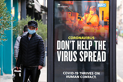 © Licensed to London News Pictures. 18/01/2021. London, UK. A man wearing a protective face covering walks past the government's 'Don't Help The Virus Spread' publicity campaign poster in north London, after the mutated variant of the SARS-Cov-2 virus continues to spread around the country. People in England aged 70 and over have started to receive offers of a coronavirus vaccine from today. The government could lift the lockdown in March, after people aged 70 and above have been vaccinated. Every adult in the UK will be offered a first dose of a coronavirus vaccine by September. Photo credit: Dinendra Haria/LNP