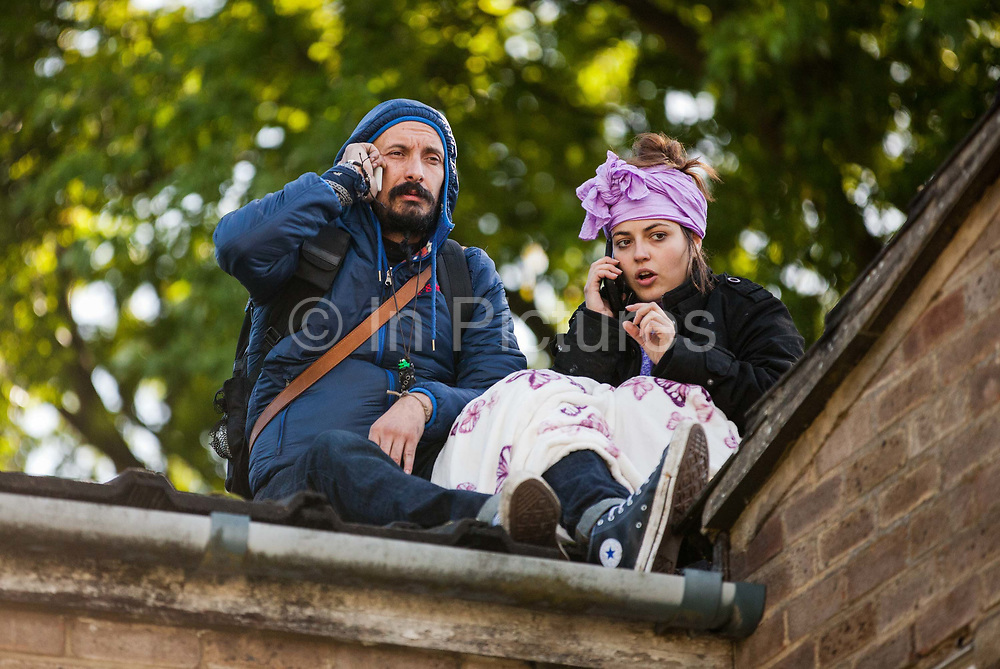 Housing activists take refuge from bailiffs trying to evict them on a roof on the Sweets Way housing estate on 23rd September 2015 in London, United Kingdom. 2nd sentence - Why. A group of housing activists calling for better social housing provision in London had occupied some of the properties on the 142-home estate in Whetstone, in some cases refurbishing properties intentionally destroyed by the legal owners following eviction of the original residents, in order to try to prevent the eviction of the last resident on the estate and the planned demolition and redevelopment of the entire estate by Barnet Council and Annington Property Ltd.