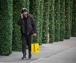 © Licensed to London News Pictures. 26/11/2020. London, UK. A shopper walks past Christmas decorations in Oxford Street, London as Health Secretary Matt Hancock reveals his plans today for a new Covid 3 tiered system of restrictions. As expected, London escape the highest restriction of Tier 3 and will be in Tier 2 with the possibility of shops, pubs and restaurants to open up again for the Christmas period. Photo credit: Alex Lentati/LNP