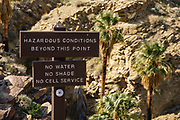 "A sign lists ""No water, no shade, and no cell service"" as ""hazardous conditions beyond this point."" Visit the world's largest California Fan Palm oasis on the beautiful Palm Canyon Trail, a great ""tour de fronds."" We hiked the Palm Canyon Trail to Indian Potrero Trail to Stone Pools, and looping back via Victor Trail, in the Indian Canyons, Palm Springs, California, USA. The Indian Canyons are the ancestral home of the Agua Caliente Band of Cahuilla Indians. California fan palms (Washingtonia filifera in the palm family Arecaceae) are native to the far southwestern United States and Baja California. Today's oasis environment was protected from a drying climate, restricting this cold-tolerant palm to widely separated relict groves. Multiple overlapping photos were stitched to make this panorama."