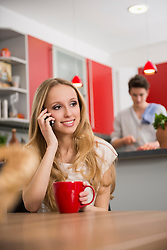 Teenager girl talking on mobile phone with man in the background at the kitchen table, Munich, Bavaria, Germany