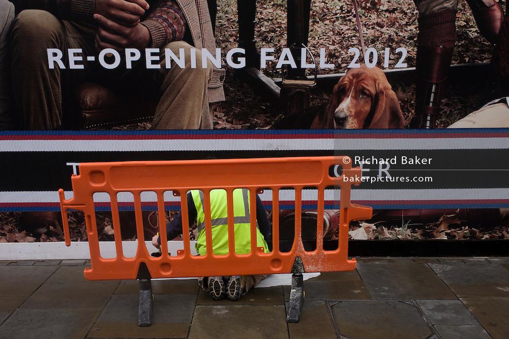 Workman paints on street pavement below Tommy Hilfiger's billboard featuring a Basset Hound dog.