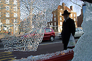 An Orthodox Jewish man in traditional clothes looks through a vandalised and smashed window in a bus shelter on the A20 Road in Stamford Hill, London, England.