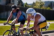 Matt Mattison, right, of Coeur d'Alene passes alongside Daniel Gregory, left, of Portland Oregon on Fourth Street nearby Coeur d'Alene High School during Sunday's Ford Ironman triathlon...