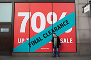 Man looking at his mobile phone on Oxford Street and interacts with large scale sale final reducion signs in red and white for major high street clothing retail shops on 21st January 2020 in London, England, United Kingdom. Oxford Street is a major road in the West End of London. It is Europes busiest shopping street, with around half a million daily visitors, and has approximately 300 shops.