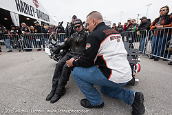 Milwaukee policeman and Harley-Davidson employee George Petropouls teaches Jackie Wallace of Plattsburgh, NY how easy it is to pick up a bike that has fallen over at the Harley-Davidson display at Daytona International Speedway on the first day of Daytona Beach Bike Week 2015. FL, USA. Saturday, March 7, 2015.  Photography ©2015 Michael Lichter.