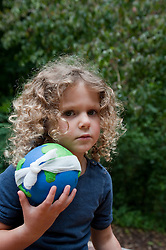 young girl holding a model of planet Earth with a bandage wrapped around it