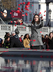 NOTE ALTERNATE CROP Laura Wright throws poppies in the fountain during an event in London's Trafalgar Square to mark Armistice Day.