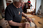Rod Ward makes accurate measurements. Violins being made at viloin an cello maker, Rod Ward's studio in Guilden Morden, Hertfordshire, UK. This highly skilled craft involves the process of making from raw wood to final instrument. All hand crafted with specialist tools and care for detail.