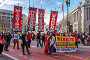 San Francisco, USA. 19th January, 2019. The Women's March San Francisco makes way down Market Street. Missing and murdered indigenous women was a prominent theme at the march and rally.  Here a group dressed in red march to bring attention to the issue in Northern California, led by the banner for a missing young woman from Covelo, California: Khadijah Britton. Credit: Shelly Rivoli/Alamy Live News
