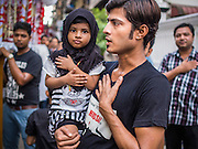 03 NOVEMBER 2014 - YANGON, MYANMAR: A Shia girl and her father beat their chests during the celebration of Ashura in Yangon Monday. Shia Muslims in Yangon started the celebration of Ashura Monday. Ashura commemorates the death of Hussein ibn Ali, the grandson of the Prophet Muhammed, in the 7th century. Hussein ibn Ali is considered by Shia Muslims to be the third Imam and the rightful successor of Muhammed. He was killed at the Battle of Karbala in 610 CE on the 10th day of Muharram, the first month of the Islamic calendar. According to Myanmar government statistics, only about 4% of Myanmar is Muslim. Many Muslims have fled Myanmar in recent years because of violence directed against Burmese Muslims by Buddhist nationalists.    PHOTO BY JACK KURTZ