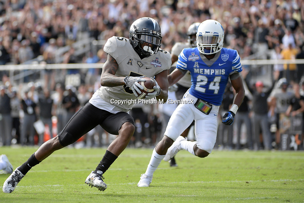 Central Florida wide receiver Dredrick Snelson (5) runs into the end zone for a touchdown in front of Memphis defensive back Tito Windham (24) after catching a pass during the first half of the American Athletic Conference championship NCAA college football game Saturday, Dec. 2, 2017, in Orlando, Fla. (Photo by Phelan M. Ebenhack)