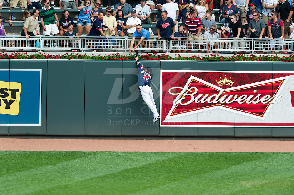 Josh Willingham (16) of the Minnesota Twins leaps unsuccessfully in an attempt to rob Delmon Young (21) of the Detroit Tigers of a home run on August 15, 2012 at Target Field in Minneapolis, Minnesota.  The Tigers defeated the Twins 5 to 1.  Photo: Ben Krause