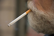close up of a man with a cigarette hanging from his mouth
