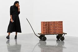 """© Licensed to London News Pictures. 11/09/2019. LONDON, UK. A staff member views """"A Pile of Bricks"""", 2019. Preview of """"Remains to be Seen"""", a new exhibition by Mona Hatoum at White Cube gallery in Bermondsey.  This is the first presentation of her work since Tate Modern in 2016.  The show runs 12 September to 3 November 2019.  Photo credit: Stephen Chung/LNP"""