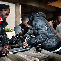 Nederland, Amsterdam , 15 december 2012..De uitgeprocedeerde asielzoekers die de afgelopen dagen onderdak kregen in de gekraakte Sint Jozefkerk in Amsterdam-West, kunnen daar tot eind maart blijven. Daarna moeten ze het pand vrijwillig verlaten, zo hebben ze met de eigenaar afgesproken in een overeenkomst die alle betrokkenen moeten ondertekenen..Schoon en veilig.Dat zei een woordvoerder van de groep die zich over de mensen ontfermt. In de kerk is plaats voor maximaal 102 uitgeprocedeerde asielzoekers. Ze hebben onder meer toegezegd de boel schoon te houden en te zorgen voor een veilig verblijf. De groep verbleef eerder met andere lotgenoten in een tentenkamp in Osdorp..Op de foto: Met vereende krachten wordt er getimmerd en gewerkt aan het maken van leefbare vertrekken binnen de kerk met en zonder hulp van vrijwilligers en professionele timmerlieden..Foto:Jean-Pierre Jans