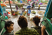 15 JUNE 2013 - YANGON, MYANMAR:  Boys sit in the door of the Yangon Circular Train as it pulls into a station. The Yangon Circular Railway is the local commuter rail network that serves the Yangon metropolitan area. Operated by Myanmar Railways, the 45.9-kilometre (28.5mi) 39-station loop system connects satellite towns and suburban areas to the city. The railway has about 200 coaches, runs 20 times and sells 100,000 to 150,000 tickets daily. The loop, which takes about three hours to complete, is a popular for tourists to see a cross section of life in Yangon. The trains from 3:45 am to 10:15 pm daily. The cost of a ticket for a distance of 15 miles is ten kyats (~nine US cents), and that for over 15 miles is twenty kyats (~18 US cents). Foreigners pay 1 USD (Kyat not accepted), regardless of the length of the journey.    PHOTO BY JACK KURTZ