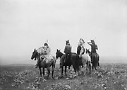 Rear view of four Crow Indians, including Shot in the Hand and Bull Chief, on horseback, Montana, 1905.  Photograph by Edward Curtis (1868-1952).