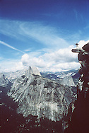 A seasonal Curry Company employee from Texas hiked with a friend to Glacier Point on their first day off in two weeks.  One of the boys ventured out to the edge of Overhanging Rock for the challenge and the wild view of the valley below.  May 1990.