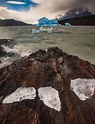 Blue iceberg, rain squalls on Lago Grey, chunks of ice blown onto rocky foreshore, Parque  Nacional Torres del Paine, Patagonia, Chile.