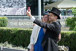 © Licensed to London News Pictures. 17/06/2014. Ascot, UK. A couple take a selfie.  Day one at Royal Ascot 17th June 2014. Royal Ascot has established itself as a national institution and the centrepiece of the British social calendar as well as being a stage for the best racehorses in the world. Photo credit : Stephen Simpson/LNP