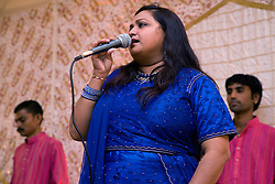 Woman in traditional costume singing during the celebration of Navratri; the Hindu festival of Nine Nights,