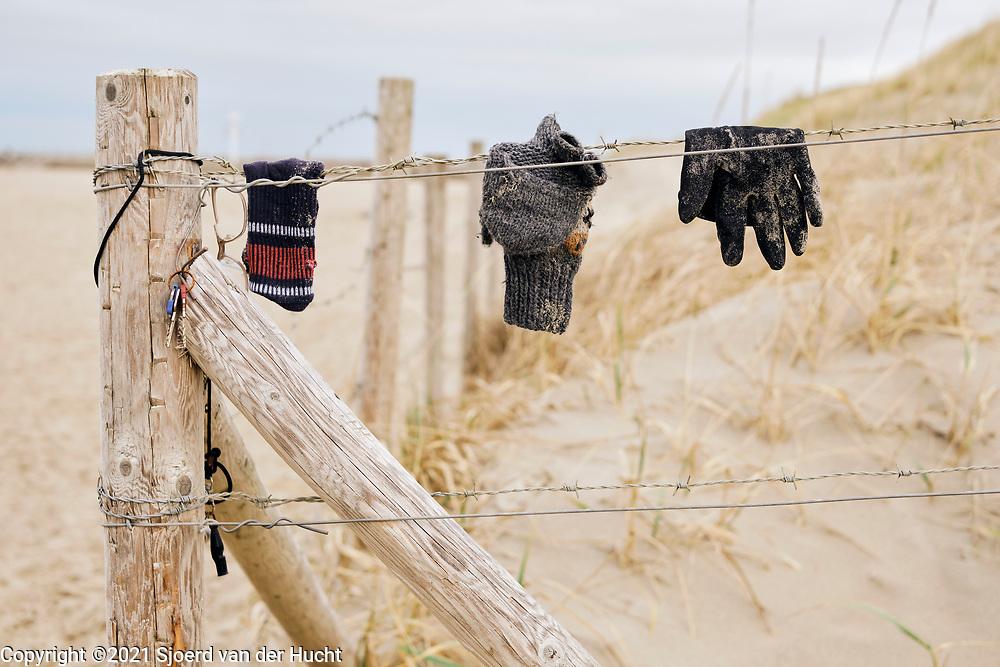 Aan het begin van het strand hangen gevonden voorwerpen aan een hek met prikkeldraad.    At the beginning of the beach, found objects hang from a barbed wire fence.