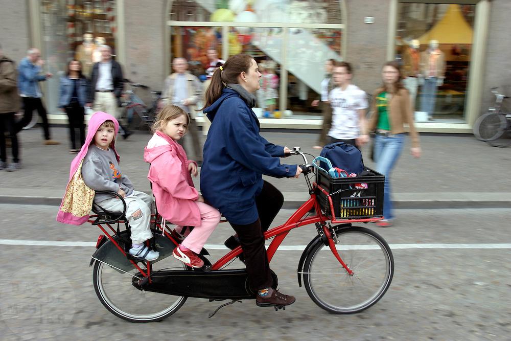 Een vrouw fietst met twee kinderen achterop door Amsterdam.<br /> <br /> A woman is cycling with two children at the back of the bike in Amsterdam.