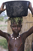 A young boy wearing a necklace and catapult, walks home after collecting water in a large metal cooking pot. Some leaves protect his head from the weight of his load. Ajiep, Bahr el Ghazal, Sudan.