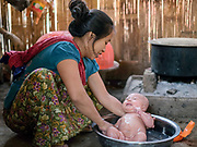 A Khi Lisu ethnic minority woman washes her baby daughter at home on 24th March 2016 in Kayah State, Myanmar