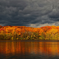 """""""Storm""""-2<br /> <br /> If you love autumn color, then let yourself delve deeply into this image of vibrant fall foliage reflected onto the Huron River below, with dark and stormy clouds above!!<br /> <br /> Autumn Landscapes by Rachel Cohen"""