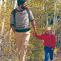 Man and boy walk between fall colored aspens in Sierra Nevada, California.