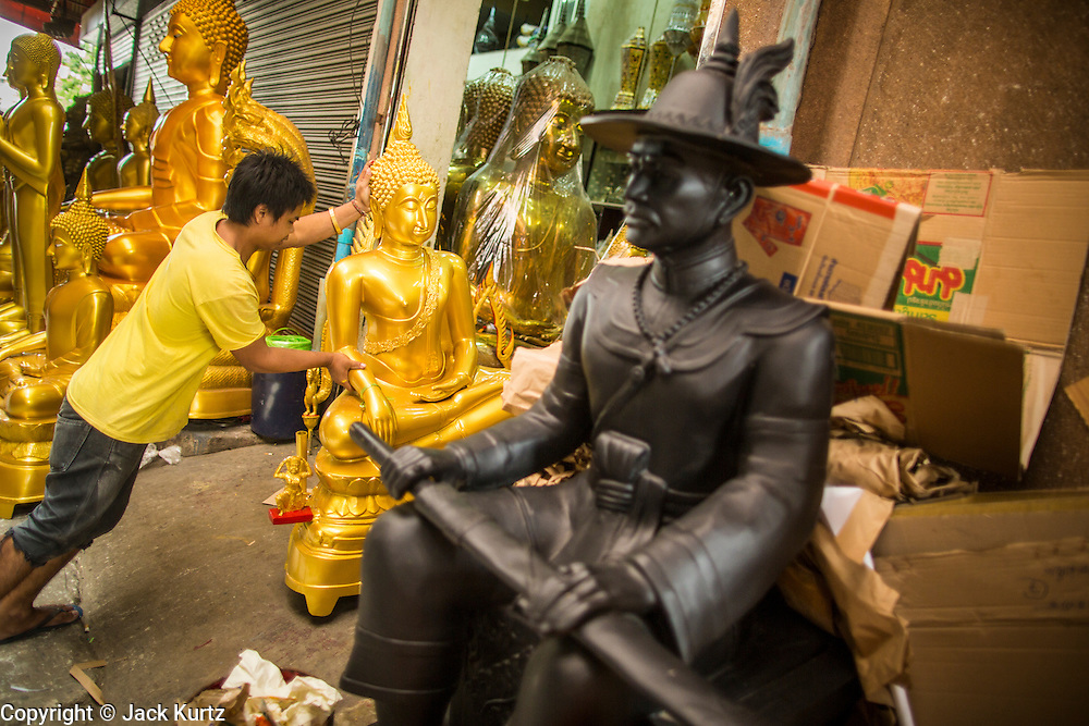 """12 NOVEMBER 2012 - BANGKOK, THAILAND:   A worker delivers a statue of the Buddha to a shop on Bamrung Muang Street in Bangkok. Thanon Bamrung Muang (Thanon is Thai for Road or Street) is Bangkok's """"Street of Many Buddhas."""" Like many ancient cities, Bangkok was once a city of artisan's neighborhoods and Bamrung Muang Road, near Bangkok's present day city hall, was once the street where all the country's Buddha statues were made. Now they made in factories on the edge of Bangkok, but Bamrung Muang Road is still where the statues are sold. Once an elephant trail, it was one of the first streets paved in Bangkok. It is the largest center of Buddhist supplies in Thailand. Not just statues but also monk's robes, candles, alms bowls, and pre-configured alms baskets are for sale along both sides of the street.    PHOTO BY JACK KURTZ"""