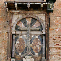 Europe, Spain, Seville. A cross decorates the facade of brick.