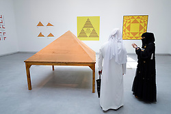 Visitors examine a sand sculpture by Gabriel Orozco on opening day of the 11th Sharjah Biennial art and cultural festival in the United Arab Emirates