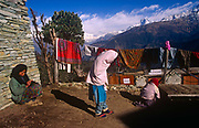 Children play outside their home with the backdrop of snow-tipped Himalayan mountain peaks, a location also serving as a trekkers rest house with hot, solar-powered showers, on 10th November 1995, in Ghorepani, Himalayas, Nepal.