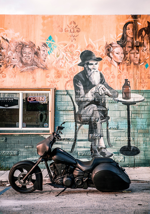 A matte black motorcycle and a mural of a Walt Whitmanesque man at The Wynwood Brewing Company in Miami.