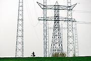 Nederland, Nijmegen, 8-11-2013Een fietser fiets over de dijk waar hoogspanningskabels overheen hangen.Foto: Flip Franssen/Hollandse Hoogte