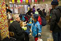 DEU, Deutschland, Germany, Berlin, 29.12.2015: Ankunft von Flüchtlingen im Bahnhof Schönefeld. Ein Freiwilliger Helfer verschafft mit seiner Handpuppe den wartenden Flüchtlingskindern etwas Freude.
