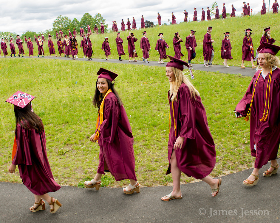 CCHS students Emma Della Volpe (center left) and Tessa Abbott proceed with their classmates during the Concord Carlisle High School graduation exercise for the Class of 2017 in Concord, June 3, 2017.   [Wicked Local Photo/James Jesson]