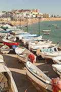 View of boats by sea with beach and city in background, Cadiz, Andalusia, Spain