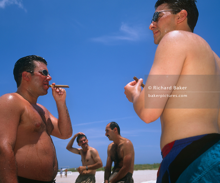 A small group of men are together on the beach just opposite to Ocean Drive on Miami Beach. Two of them are in the foreground and each wear sun glasses, each holding cigars that may be Cuban in origin, a popular source of tobacco leaf in this region of America. They have recently been immersed in the sea and water drips down their rather flabby bodies with the gentleman on the left sucking on his cigar with a belly that expands around his tanned midriff. It is intensely bright, sunny day on the sand, seen behind. Flash has emphasized the water drips and the male sweat and we also see a very clear blue tropical sky.