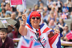 Trafalgar Square, London, June 12th 2016. Rain greets Londoners and visitors to the capital's Trafalgar Square as the Mayor hosts a Patron's Lunch in celebration of The Queen's 90th birthday. PICTURED: A woman waves her flag as the sun begins to shine.