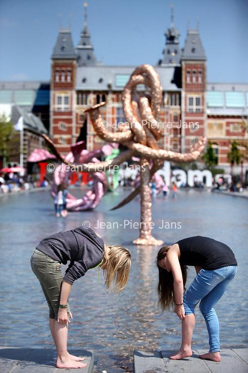 Nederland, amsterdam , 28 mei 2013.<br /> Zomerse dag in Amsterdam. <br /> Pootje baden in de vijver voor het Rijksmuseum.<br /> A rare sunny day in Amsterdam, Museumplein. People paddling in the pond.