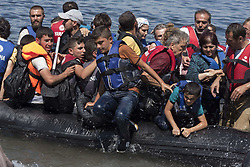 Aug. 25, 2015 - Lesbos, Greece - Refugees disembark from a boat after making the five mile crossing from Turkey. More than 30,000 refugees have reached the Greek island of Lesvos during August 2015, according to Amnesty International. (Credit Image: © Nikolas Georgiou/ZUMA Wire)