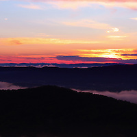 """""""Call of the Mountains""""<br /> <br /> A vibrant sunset and silhouette as clouds sweep across the top of the Blue Ridge Mountains of Virginia at sundown<br /> <br /> The Blue Ridge Mountains by Rachel Cohen"""