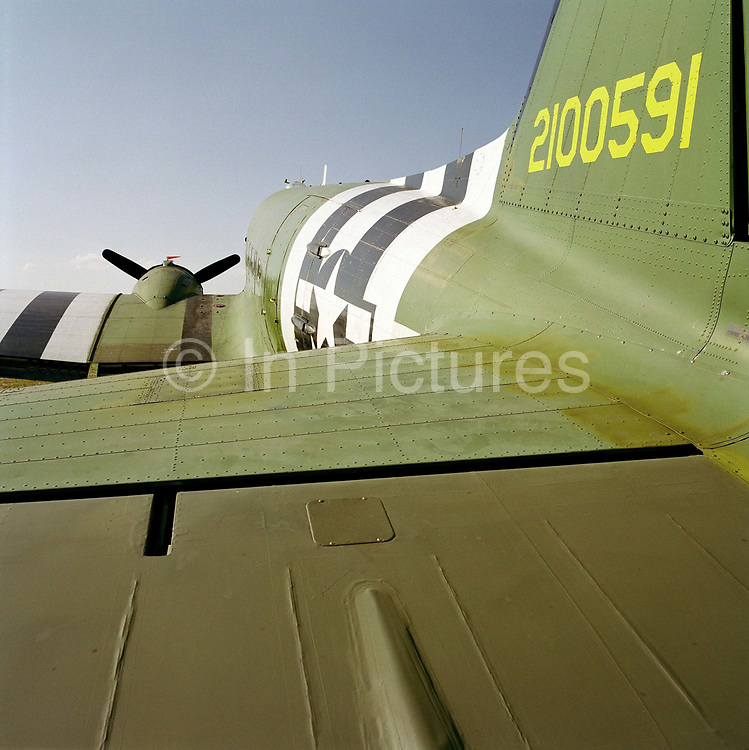 """A view along the fuselage of a DC3 Dakota, from its tail aileron to its propeller. Pointing upwards as it sits on a low tail wheel and with one of its 4 propellers still against a blue sky, we see the plane painted in the colours that many appeared in during the D-Day landings in June 1944, from where paratroopers jumped out for the eventual invasion of German-occupied France. The Douglas DC-3 is a fixed-wing propeller-driven airliner. Its speed and range revolutionized air transport in the 1930s and 1940s. Its lasting impact on the airline industry and World War II makes it one of the most significant transport aircraft ever made. Many DC-3s and converted C-47s are still used in all parts of the world. The designation """"DC"""" stands for """"Douglas Commercial""""."""